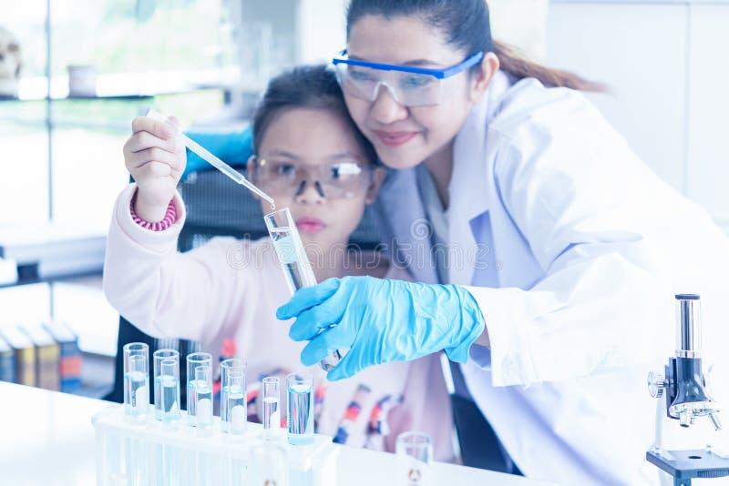 Enfants asiatiques analysant le microscope de évaluation d'étude avec des chercheurs de soins de santé de scientifique faisant de image stock