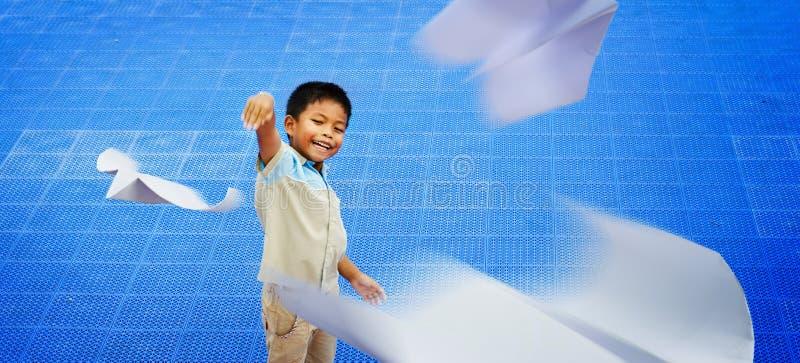 Enfants asiatiques jouant l'avion de papier image stock