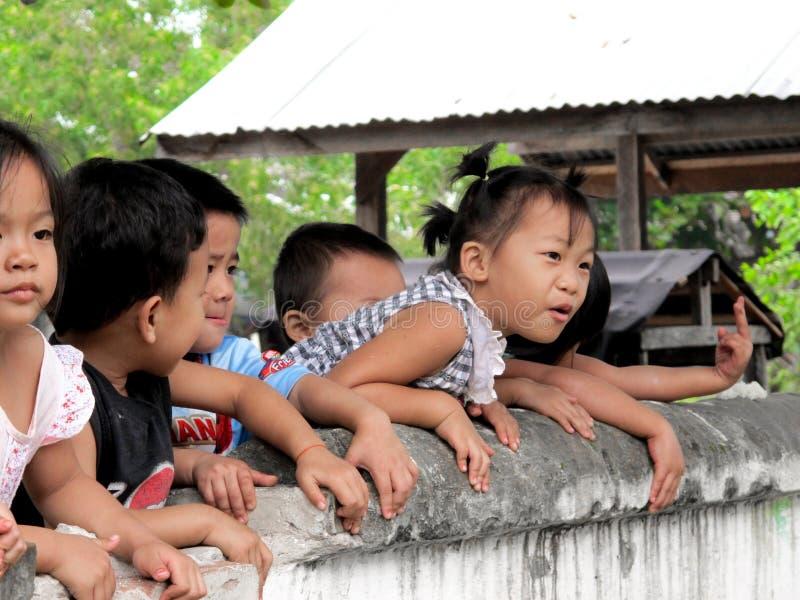 Enfants asiatiques jouant sur le mur d'école photographie stock
