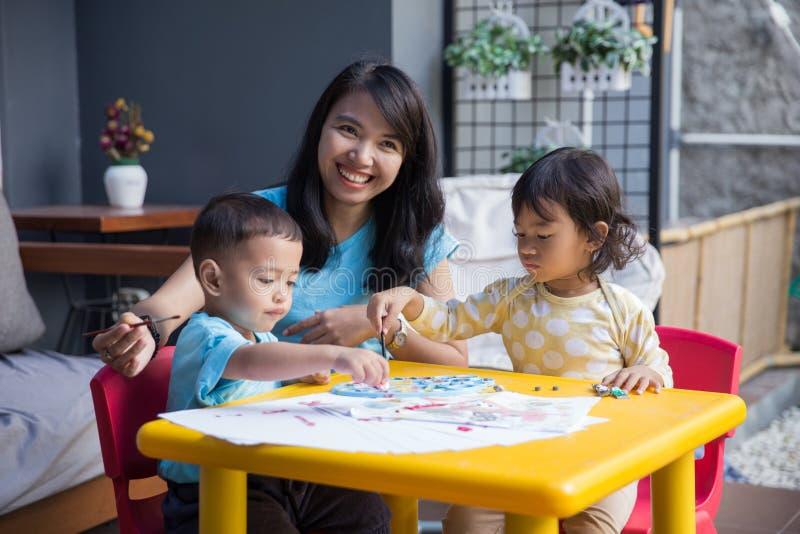 Enfants asiatiques peignant et dessinant photo stock