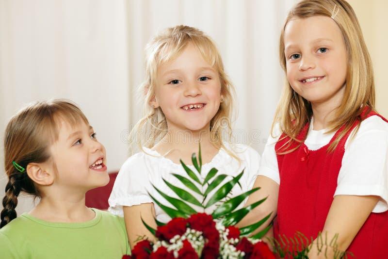 Enfants attendant avec des fleurs la mère image libre de droits