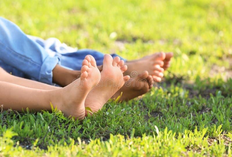 Enfants aux pieds nus mignons se trouvant sur l'herbe dehors images stock