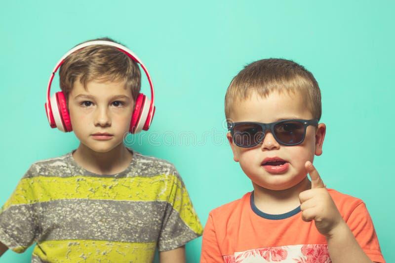 Enfants avec des casques et des lunettes de soleil de musique photographie stock libre de droits