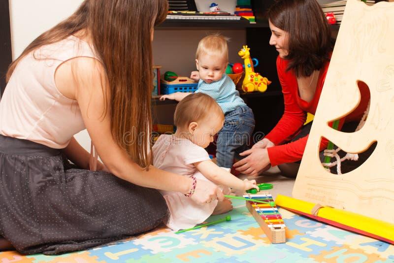 Enfants avec des mères dans la salle de jeux photographie stock