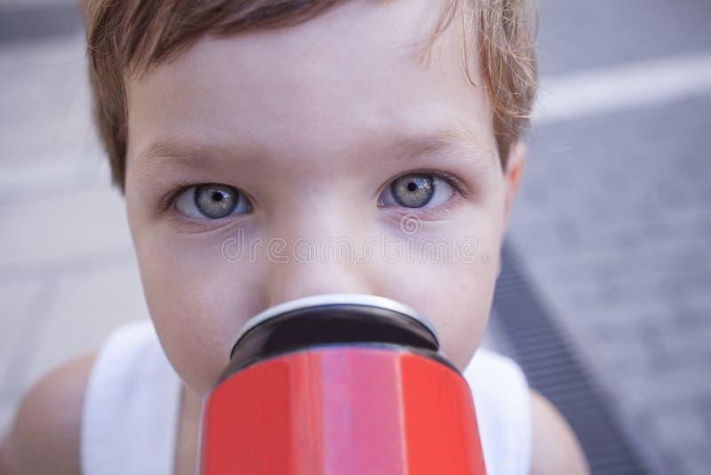 Enfants avec l'habitude malsaine au sujet des boissons non alcoolisées sucrées photographie stock