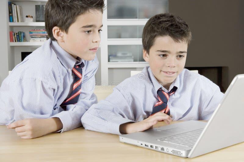 Enfants avec l'ordinateur portable à la maison photos stock