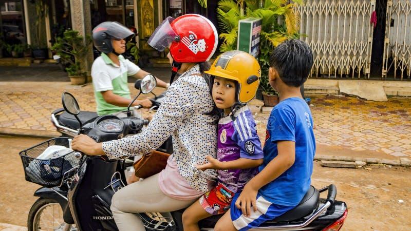 Enfants avec la femelle sur le scooter photos stock