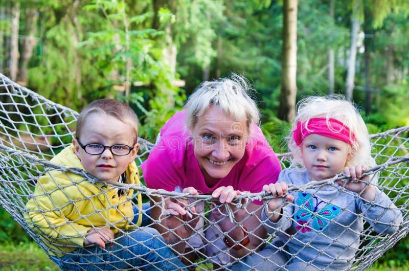 Enfants avec la grand-mère balançant dans un hamac photographie stock