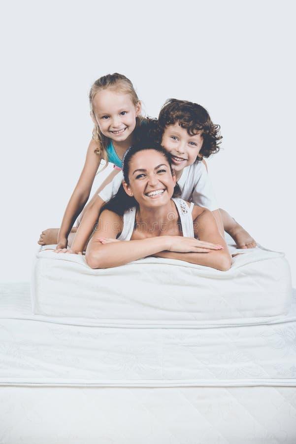 Enfants avec la mère se trouvant sur la pyramide du matelas photos stock