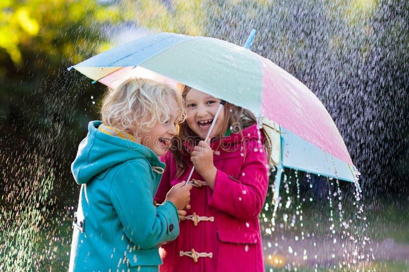 Enfants avec le parapluie jouant sous la pluie de douche d'automne photos stock