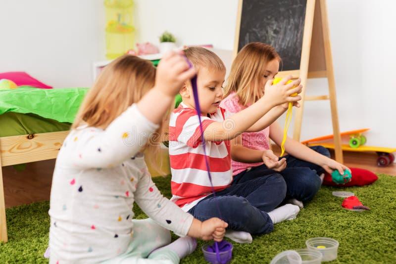 Enfants avec modeler l'argile ou des humeurs visqueuses à la maison photos libres de droits