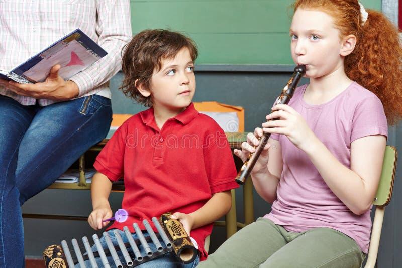 Enfants ayant des leçons de musique à l'école photographie stock libre de droits