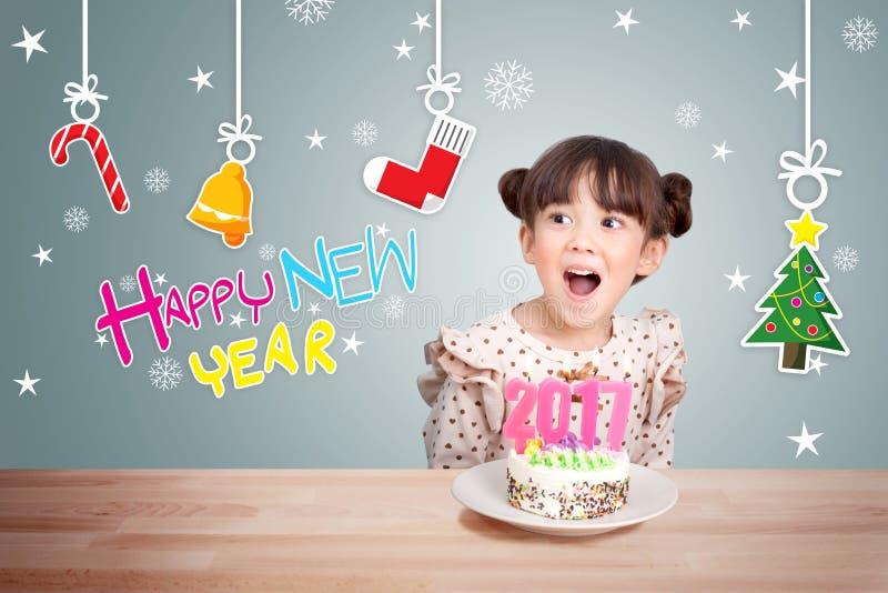 Enfants ayant l'amusement à la partie de nouvelle année avec le gâteau et la bougie 2017 photo libre de droits