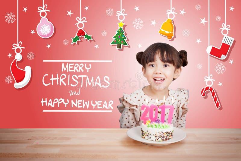 Enfants ayant l'amusement à la partie de nouvelle année avec le gâteau et la bougie 2017 photo stock
