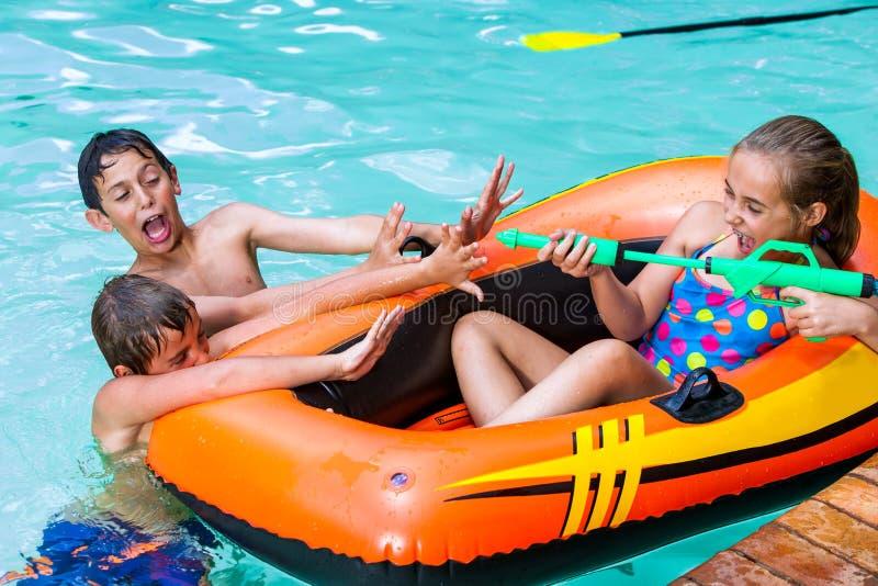 Enfants ayant l'amusement avec l'arme à feu d'eau. photos stock