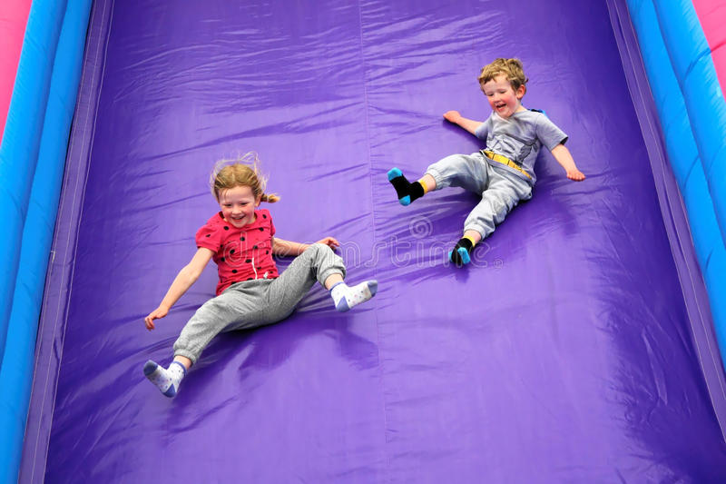 Enfants ayant l'amusement sur la glissière photos libres de droits