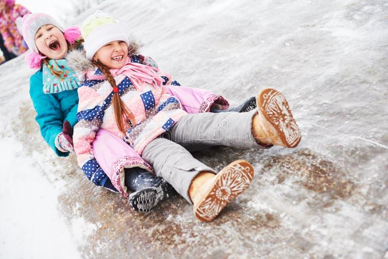 Enfants ayant la glissière de glace d'équitation d'amusement en hiver photographie stock libre de droits