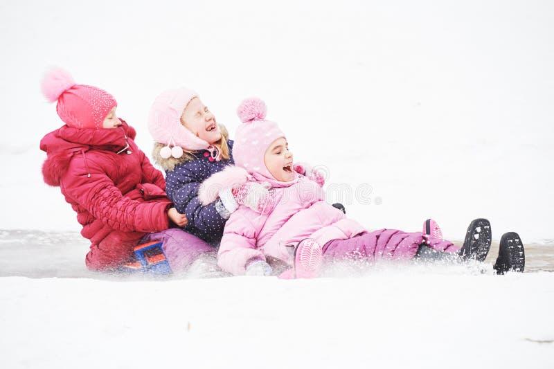 Enfants ayant la glissière de glace d'équitation d'amusement en hiver photos libres de droits