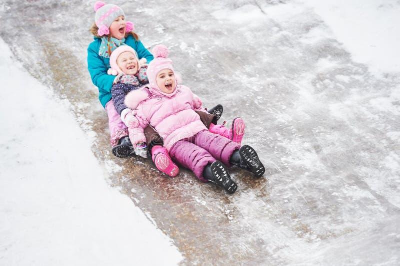 Enfants ayant la glissière de glace d'équitation d'amusement en hiver images libres de droits