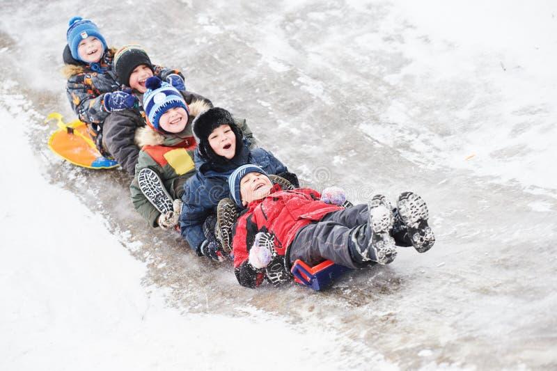 Enfants ayant la glissière de glace d'équitation d'amusement en hiver de neige photographie stock