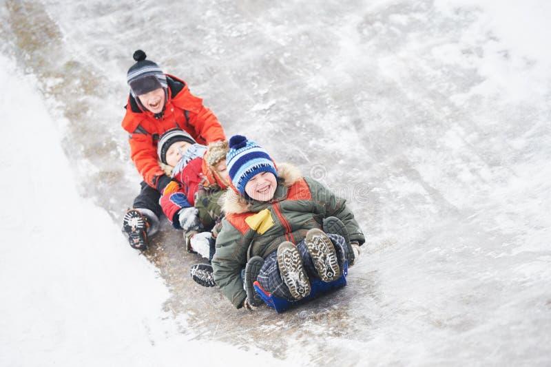 Enfants ayant la glissière de glace d'équitation d'amusement en hiver image stock