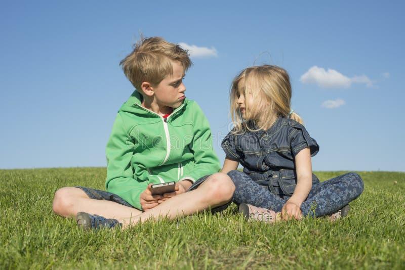 Enfants blonds heureux à l'aide du smartphone (jeu de observation de film ou de jouer) se reposant sur l'herbe image stock
