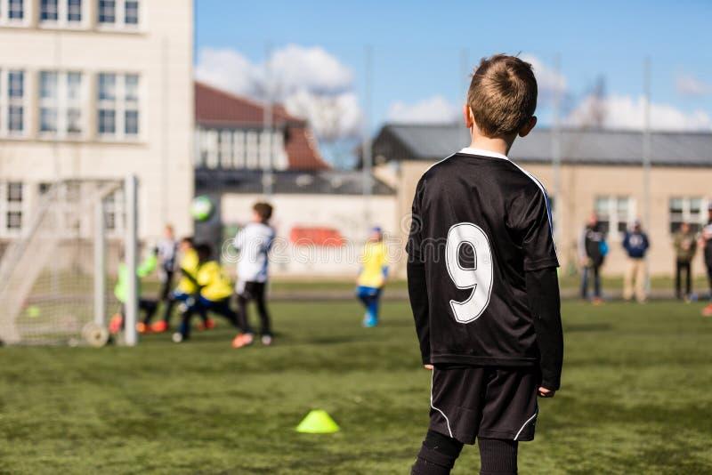 Enfants brouillés jouant le football photographie stock