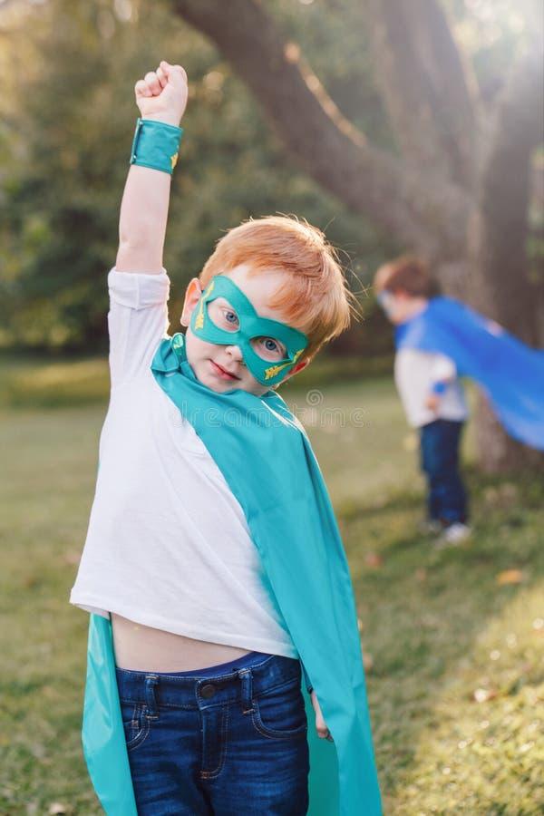 Enfants caucasiens préscolaires jouant des super héros photos libres de droits