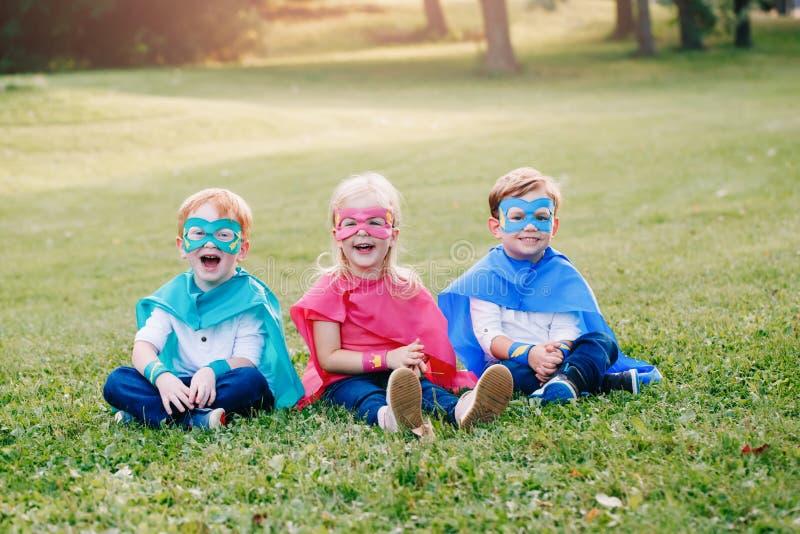 Enfants caucasiens pr?scolaires jouant des super h?ros photo libre de droits