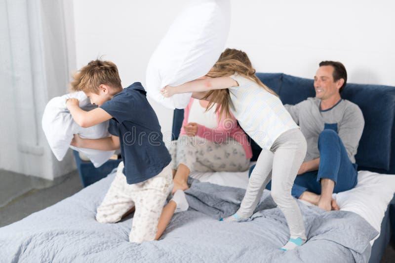 Enfants combattant les oreillers, la famille ayant la chambre à coucher d'amusement, les parents avec la fille et le fils gai ens photo stock
