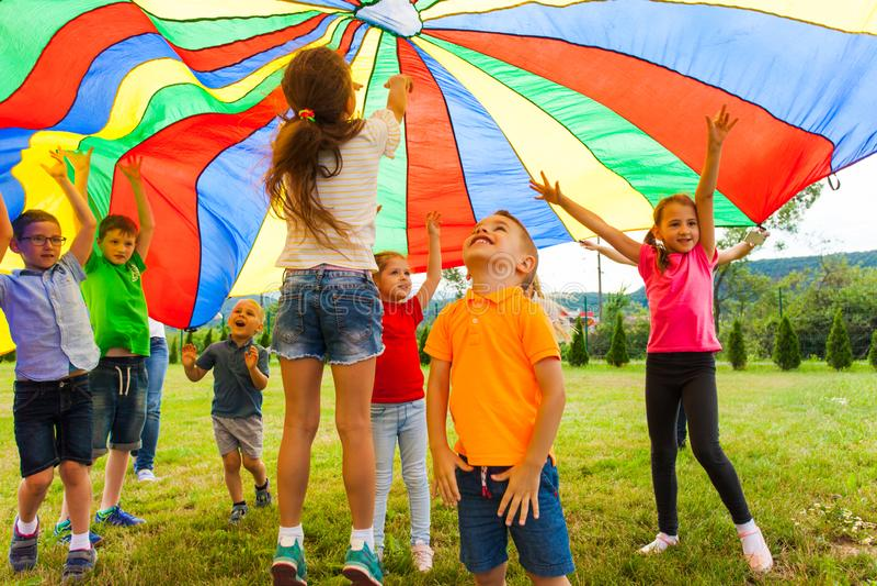 Enfants comblés rebondissant sous le textile d'auvent d'arc-en-ciel image stock