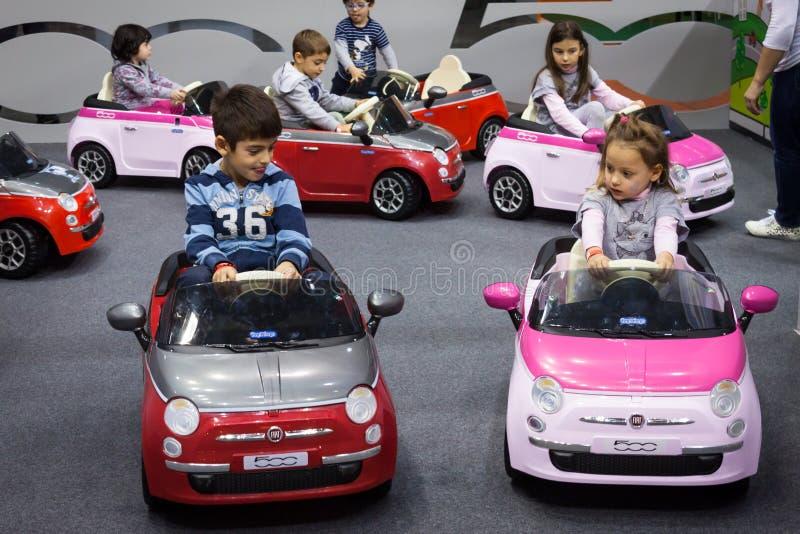 Enfants conduisant les voitures électriques à G ! venez le giocare à Milan, Italie photographie stock