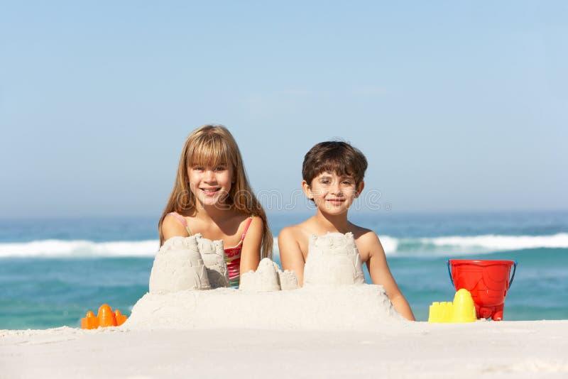 Enfants construisant des pâtés de sable des vacances de plage photos stock