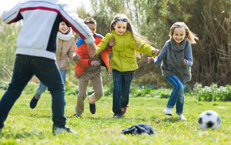 Enfants courant après boule photos stock