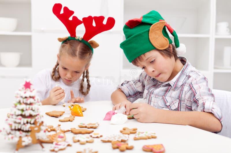 Enfants décorant des biscuits de pain d'épice images libres de droits