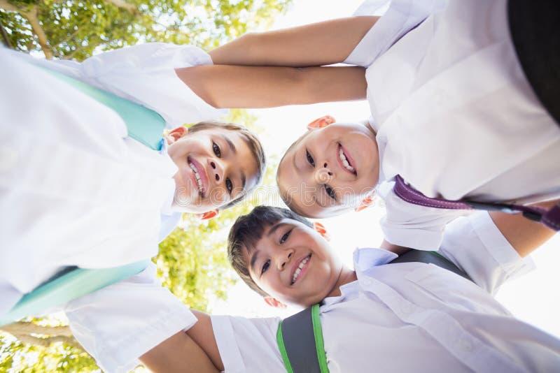 Enfants d'école formant le petit groupe dans le campus image stock
