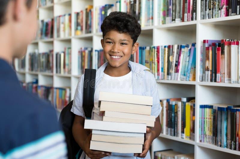 Enfants d'école primaire dans la bibliothèque photographie stock libre de droits