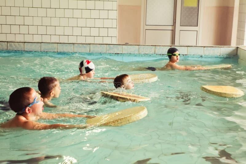 Enfants d'école primaire dans la leçon de natation de qualifications images stock