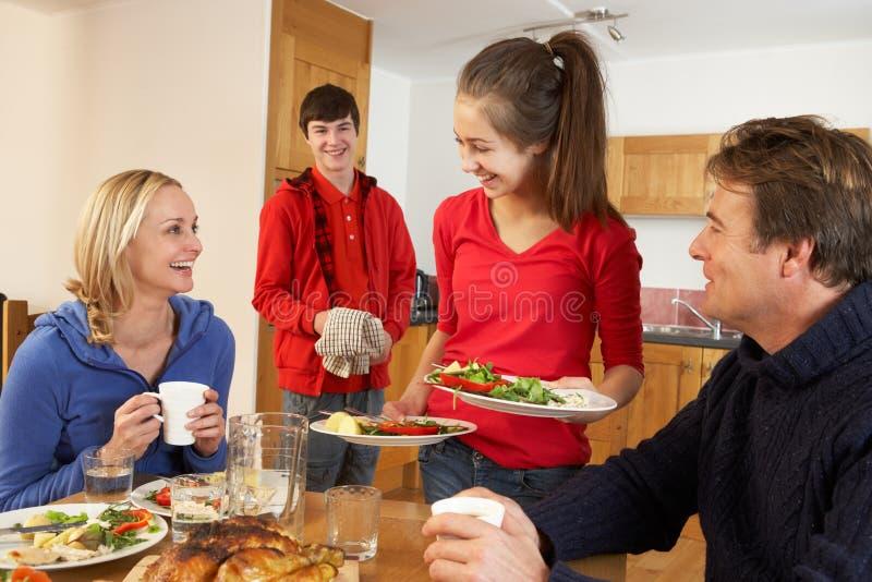 Enfants d'adolescent utiles servant la nourriture aux parents image stock