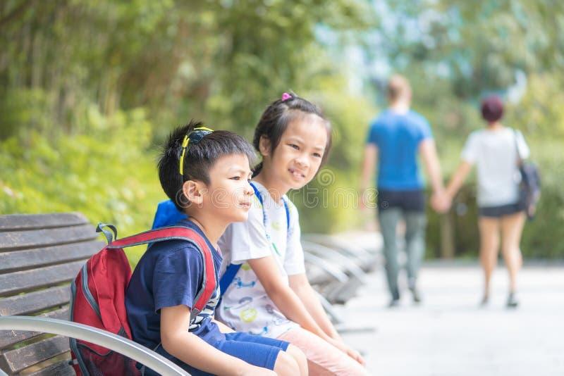 Enfants d'enfant de mêmes parents s'asseyant en parc de Kowloon image stock