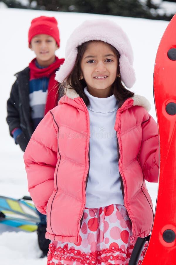 Enfants d'Indien est toboganning dans la neige image libre de droits