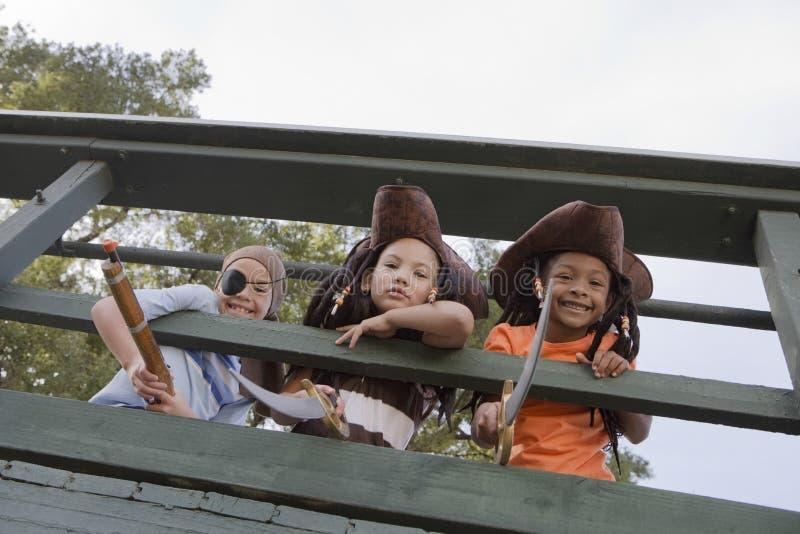 Enfants dans des costumes regardant par les balustrades en bois photographie stock