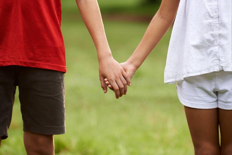 Enfants dans l'amour, garçon et fille tenant des mains photos stock