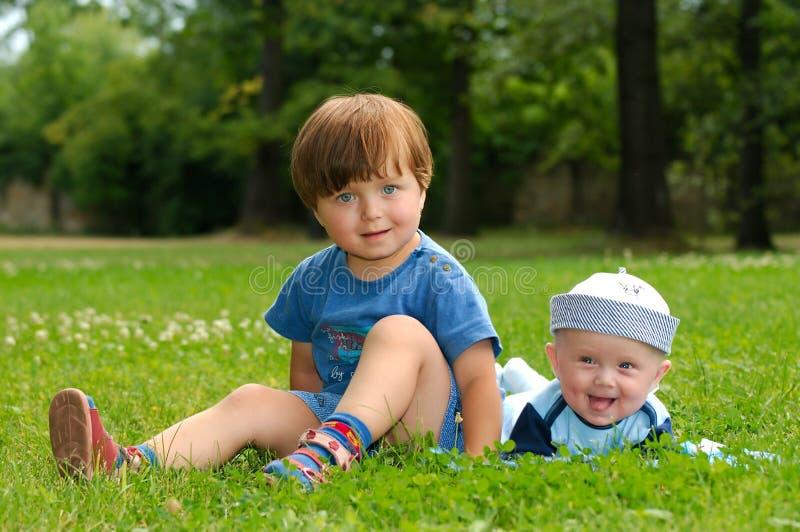 Enfants dans l'herbe photo stock