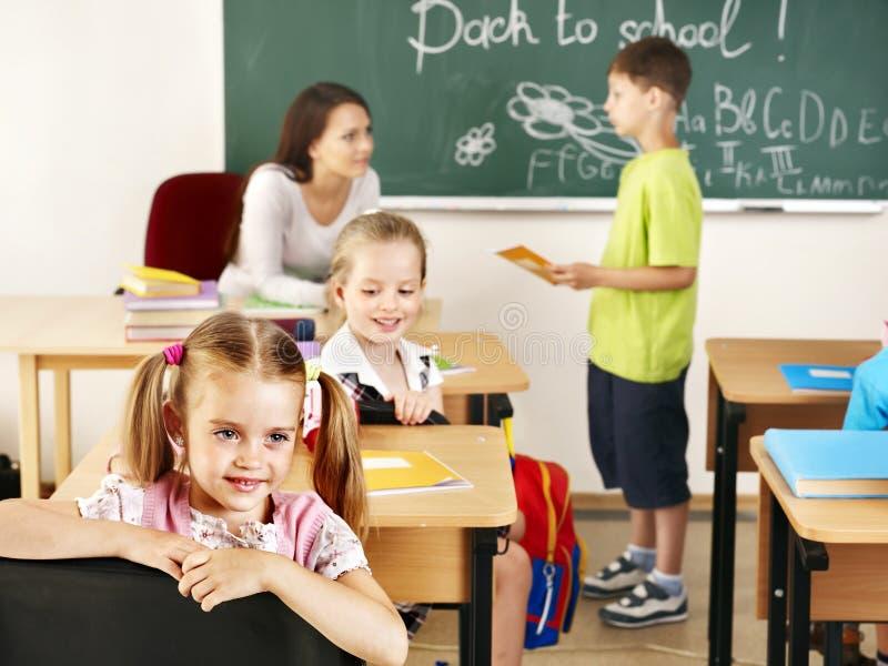 Enfants dans la salle de classe près du tableau noir. photos stock