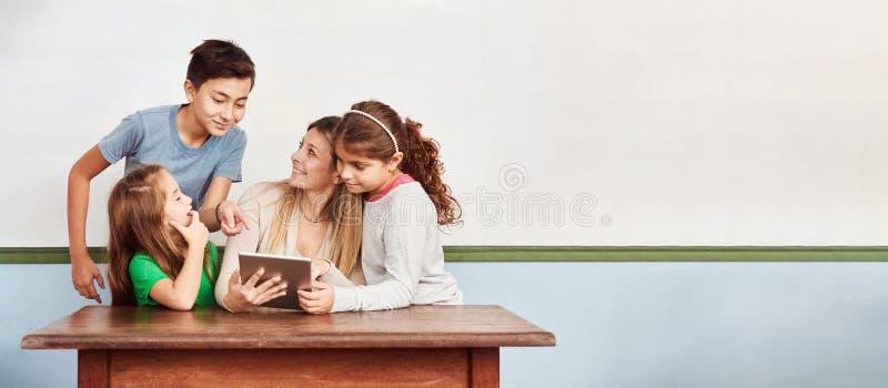 Enfants dans la salle de classe sur l'Internet avec la tablette photographie stock