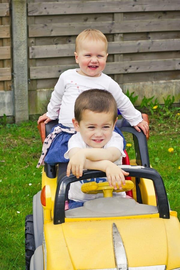 Enfants dans la voiture de jouet photographie stock