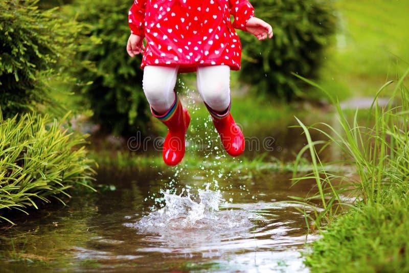 Enfants dans le magma sous la pluie d'automne Usage imperméable photos libres de droits