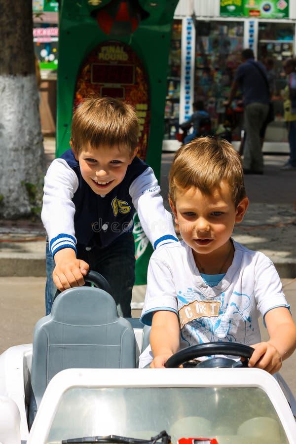 Enfants dans le terrain de jeux montant une voiture de jouet Nikolaev, Ukraine photo stock