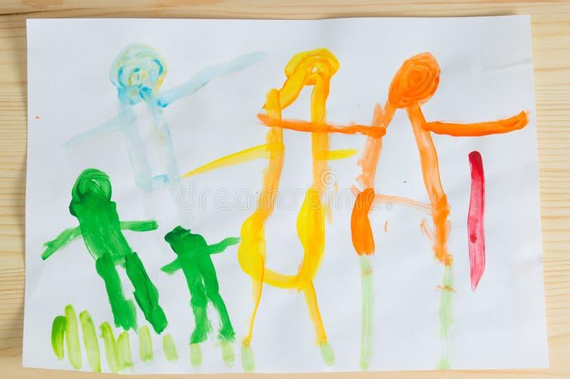 enfants de 3 ans dessinant la photo heureuse de famille sur la table en bois À photos stock